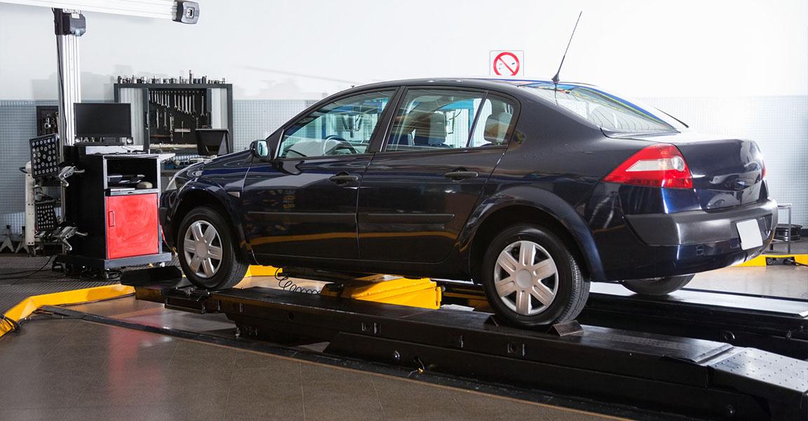 Dark blue sedan in workshop on platform