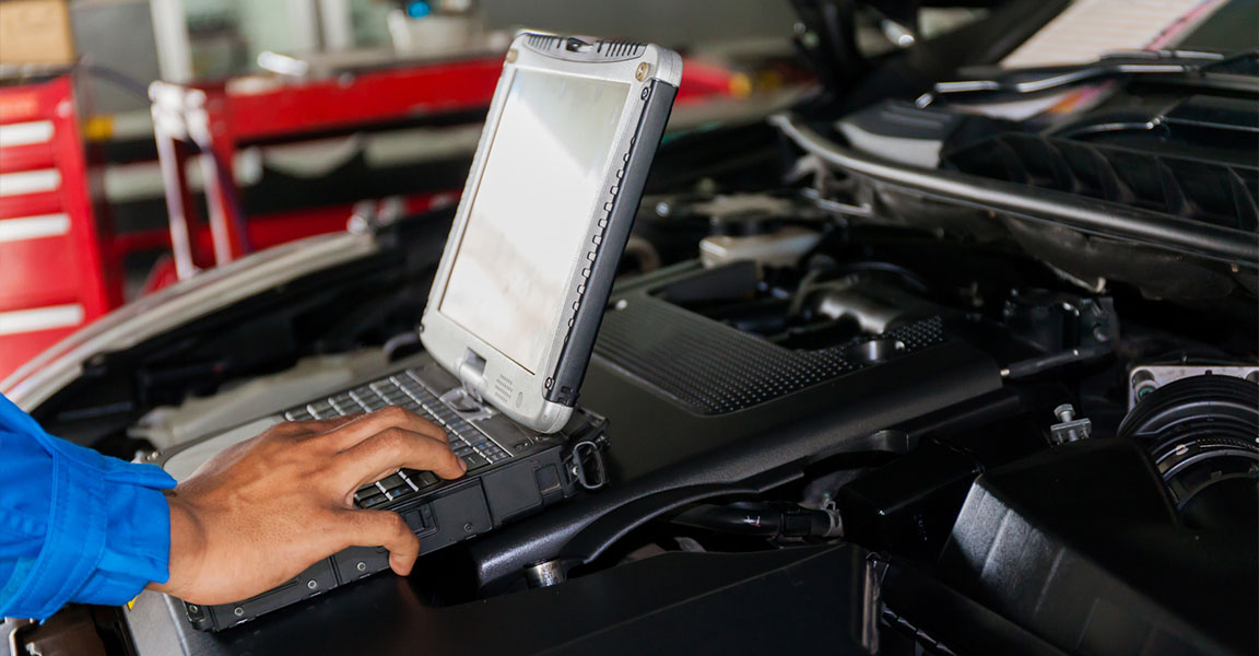 mechanic performing diagnostics on car with laptop