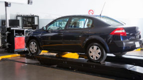 Dark blue sedan in workshop on platform